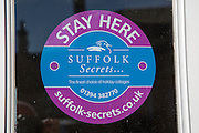 Close up of holiday cottage advertising sign,  Suffolk Secrets, England, UK