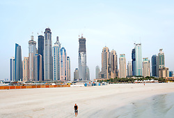 Man jogging on beach at Jumeirah Beach resort with skyline of Marina in distance in Dubai UAE
