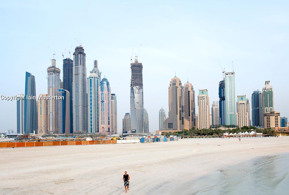 Man jogging on beach at Jumeirah Beach resort with skyline of Marina in distance in Dubai UAE