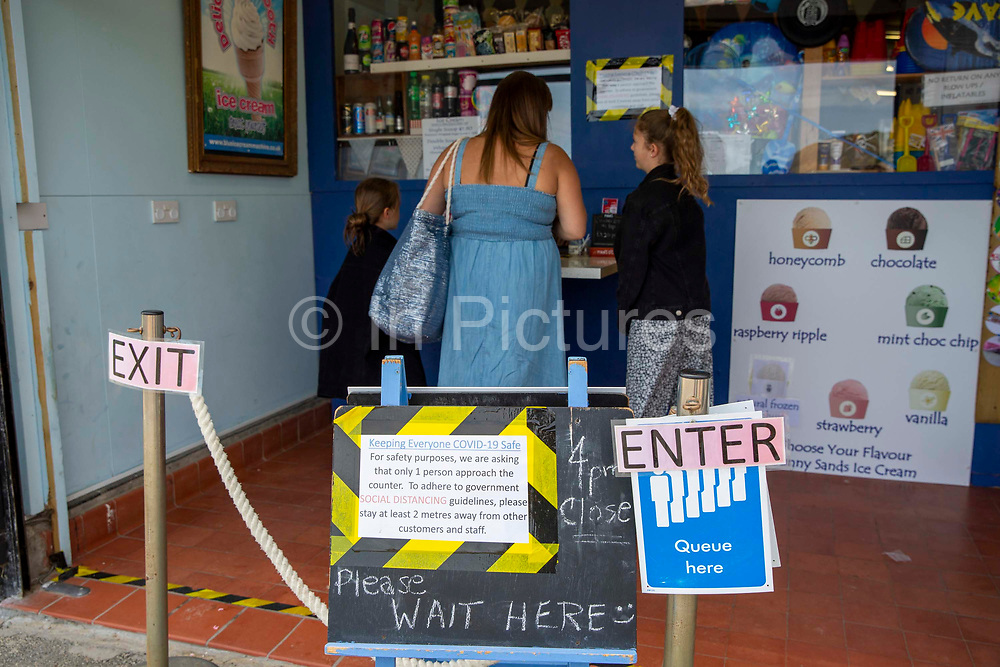A woman and her two daughters get ice-cream from the Sunny Sands Kiosk on the 7th of July 2020 in Folkestone, United Kingdom. Non essential retails business could re-open on the 15th of June as long as they were COVID safe. This kiosk has a Clea entrance and exit to comply with social distancing rules.