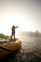 Young man fly fishing while on a whitewater raft trip on the Chilko River. British Columbia, Canada.