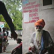 Elderly man sitging outside a stockyard in Amritsar.