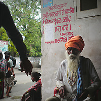 Elderly man sitging outside a stockyard in Amritsar.