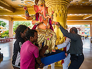 "05 SEPTEMBER 2016 - BANGKOK, THAILAND:  Men carry a statue of Ganesha into the prayer hall on the first day of Ganesha Chaturthi celebrations at Shiva Temple in Bangkok. Ganesha Chaturthi also known as Vinayaka Chaturthi, is the Hindu festival celebrated on the day of the re-birth of Lord Ganesha, the son of Shiva and Parvati. The festival, also known as Ganeshotsav (""Festival of Ganesha"") is observed in the Hindu calendar month of Bhaadrapada. The date usually falls between 19 August and 20 September. The festival lasts for 10 days, ending on Anant Chaturdashi. Ganesha is a widely worshipped Hindu deity and is revered by many Thai Buddhists. Ganesha is widely revered as the remover of obstacles, the patron of arts and sciences and the deva of intellect and wisdom.     PHOTO BY JACK KURTZ"