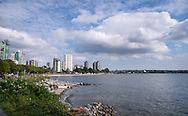 View of the Vancouver shoreline from Stanley Park, summer clouds passing over the rocky beach and water with skyscrapers in the distance.