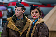 Re-enactors in WWII uniforms watch the Red Arrows - The Duxford Battle of Britain Air Show is a finale to the centenary of the Royal Air Force (RAF) with a celebration of 100 years of RAF history and a vision of its innovative future capability.