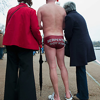 LONDON, ENGLAND - DECEMBER 25:  A member of the Serpentine Swimming Club meets friends after swimming in the icy Serpentine waters during the annual Christmas Day Peter Pan Cup on December 25, 2009 in London, England.  The traditional 100 yards Christmas race got its name in 1904 after Sir James Barrie presented the first Peter Pan Cup and is only open to club members who have competed in at least three of the winter series races.   (Photo by Marco Secchi/Getty Images)