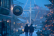 USA, Newport, RI - Couple walks through the snow on Bowen's wharf decorated for the holidays.