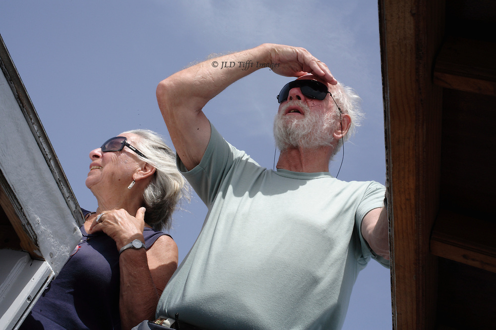 Portrait of a windblown middle aged couple wearing sunglasses and sailing in the sunshine.  View from the cabin below deck through the companionway. White-bearded man shades his face with one hand.