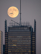 A plane is passing the moon over the Hudson Yards modern building complex in New York City harbor..