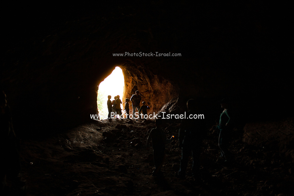 A group of people explore a cave. Photographed in the Carmel mountain range, Israel