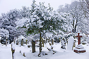 Snow-covered gravestones in Hampstead Parish Graveyard in Church Row and Holly Place in Hampstead, North London, UK