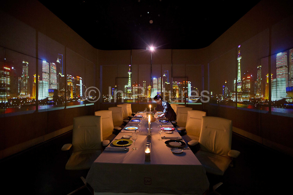 Waiters prepare for dinner as projections adorn the dining room wall of Chef Paul Pairet's Ultra Violet (UV) restaurant in Shanghai, China on 28 September 2013. Serving only a dozen patrons per meal, UV is quickly making a reputation for itself as it combines the senses of taste, sound, and sight to the extreme.