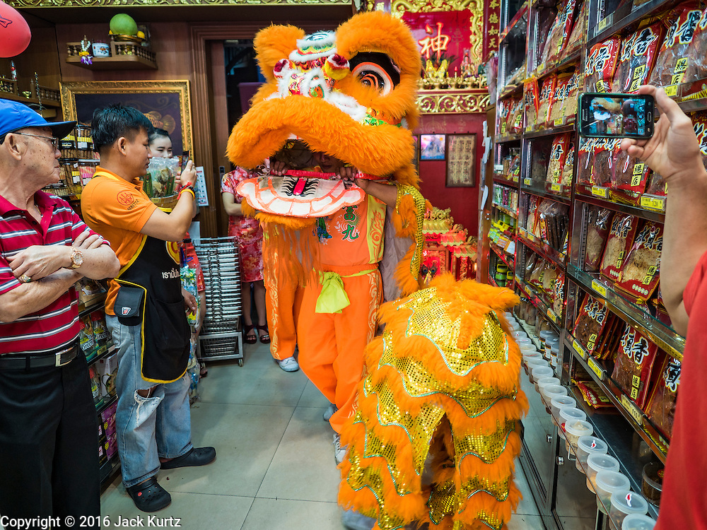 """08 FEBRUARY 2016 - BANGKOK, THAILAND:  Lion dancers perform inside a small Chinese grocery shop for Chinese New Year on Yaowarat Road in Bangkok's Chinatown district, during the celebration of the Lunar New Year. Chinese New Year is also called Lunar New Year or Tet (in Vietnamese communities). This year is the """"Year of the Monkey."""" Thailand has the largest overseas Chinese population in the world; about 14 percent of Thais are of Chinese ancestry and some Chinese holidays, especially Chinese New Year, are widely celebrated in Thailand.      PHOTO BY JACK KURTZ"""