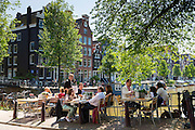Diners dining al fresco at pavement canalside cafe by Brouwersgracht and Herengracht canal, Jordaan district, Amsterdam, Holland