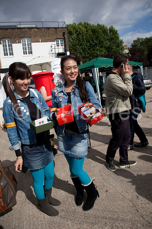 Two Japanese artists dressed in the same clothes selling their small pieces. The Art Car Boot Fair in a car park just off Brick Lane in East London. This is an alternative art event where artists show their works and engage with the public. The Art Car Boot Fair was an idea that grew out of a desire to re-introduce some summer fun and frivolity into a thriving but increasingly commercial London art scene. The aim for the Art Car Boot Fair is to be a day when the artists let their hair down and for all-comers to engage with art in a totally informal way, and to pick up some real art bargains.