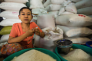 14 JUNE 2013 -  PATHEIN, AYEYARWADY, MYANMAR: A rice vendor in the market in Pathein, Myanmar. Pathein, sometimes also called Bassein, is a port city and the capital of the Ayeyarwady Region, Burma. It lies on the Pathein River (Bassein), which is a western branch of the Irrawaddy River. It's the fourth largest city in Myanmar (Burma) about 190 km west of Yangon.   PHOTO BY JACK KURTZ
