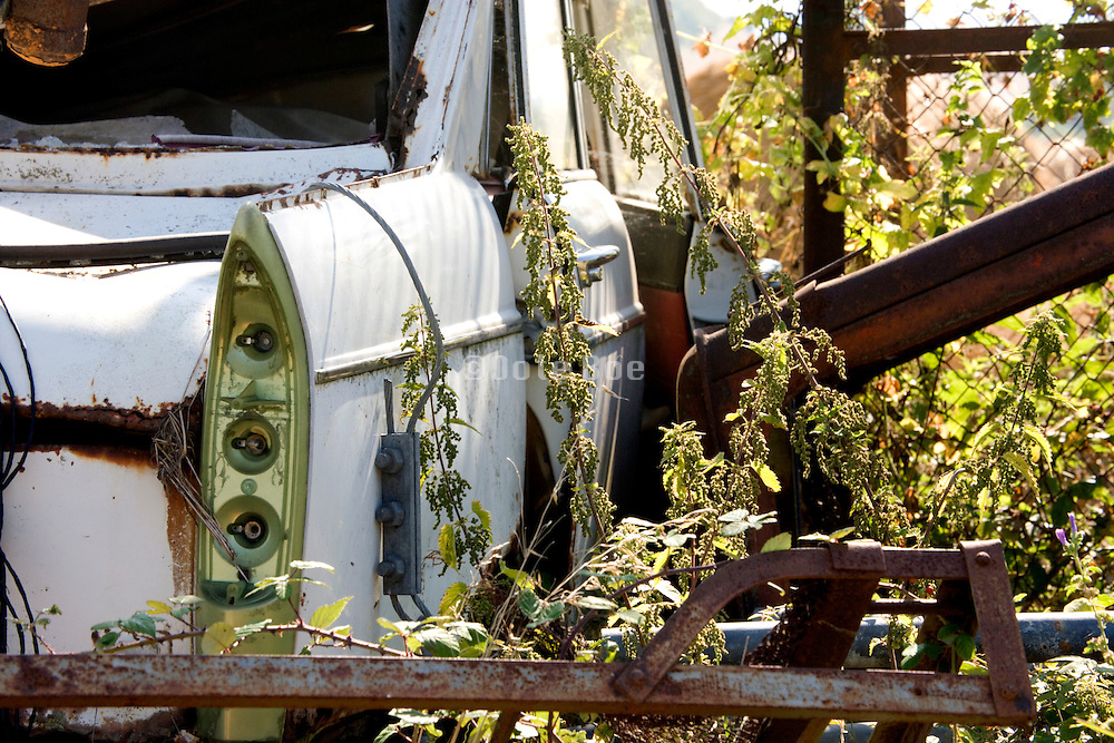 old abandoned car and other old metal halve overgrown with wild grass