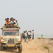 CAPTION: Villagers cram together on the roof of a vehicle in order to travel between their island and the nearby city of Patna. LOCATION: Diara Rasulpur, Saran District, Bihar, India. INDIVIDUAL(S) PHOTOGRAPHED: N/A.