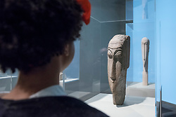 """© Licensed to London News Pictures. 21/11/2017. London, UK.  A staff member views one of several """"Head"""" sculptures.  """"Preview of """"Modigliani"""", the most comprehensive exhibition of works by Amedeo Modigliani ever held in the UK.  On display are iconic portraits, sculptures and 12 nudes, the largest group ever shown in the UK.  The show runs 23 November to 2 April 2018.  Photo credit: Stephen Chung/LNP"""