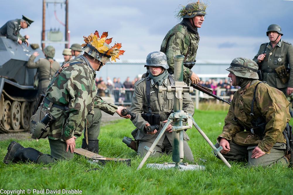 Re-enactors portrayiing panzer grenadiers prepare a replica 81mm mortar during a battle battle re-enactment in on Pickering Showground<br /> <br /> 17/18 October 2015<br />  Image © Paul David Drabble <br />  www.pauldaviddrabble.co.uk