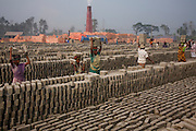 Girls carry bricks at the JRB brick factory near Sonargaon, outside Dhaka, Bangladesh. The heavy clay soils along the river near the market town of Sonargaon are well suited for making bricks. At the JRB brick factory, workers of all ages move raw bricks from long, stacked rows, where they first dry in the sun, to the smoky coal-fired kilns. After being fired, the bricks turn red. A foreman keeps tally, handing the workers colored plastic tokens corresponding to the number of bricks they carry past him. They cash in the chips at the end of each shift, taking home the equivalent of $2 to $4 (USD) a day.