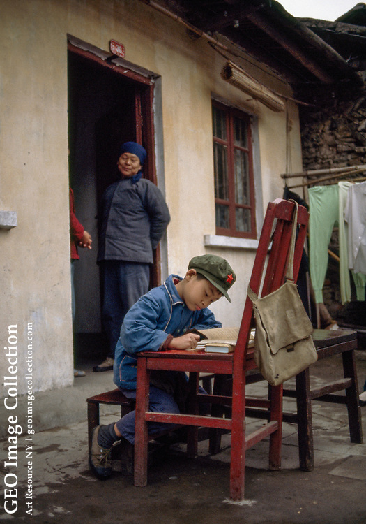 Chinese boy studying as adults look on.