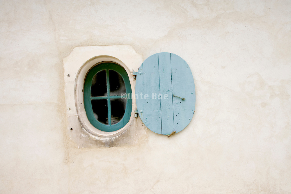 a round window with open shutter set in an renovated old wall