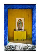 """SHOT 2/13/19 10:54:01 AM - A small but brightly colored capilla featuring Nuestra Senora de Guadalupe in the jungle near Chemax, Mexico. Chemax, from the Mayan word meaning """"tree of monkeys"""", is a small town located in the east side of Yucatan State of Mexico. Capillas, or tiny chapels, are common along the roads and highways in Mexico, which is largely Catholic. The capillas are often dedicated to certain patron saints, such as Nuestra Se√±ora de Guadalupe. Often times they contain prayer candles, pictures, personal artifacts or notes. (Photo by Marc Piscotty / © 2019)"""