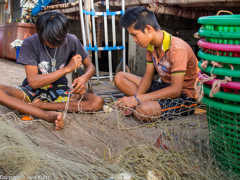 11 APRIL 2014 - PHANTHAI NORASING, SAMUT SAKHON, THAILAND: Workers repair fishing nets in Phanthai Norasing, Samut Sakhon province. Samut Sakhon is a coastal province southwest of Bangkok. It's known for its fishing and aquaculture industries but manufacturing companies are buying large plots of lands and building factories in the province, supplanting the traditional industries. A large number of Burmese migrants who work in the fishing and manufacturing sectors live in Samut Sakhon.      PHOTO BY JACK KURTZ