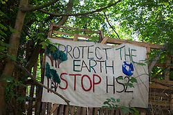 Wendover, UK. 16th June, 2021. A banner is pictured outside Stop HS2's Wendover Active Resistance Camp alongside the A413. Large areas of land around Wendover in the Chilterns AONB have already been cleared of trees and vegetation for the HS2 rail infrastructure project in spite of concerted opposition from local residents and environmental activists.