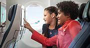 Une hôtesse avec un enfant voyageant non accompagné à bord d'un avion de la compagnie aérienne Aircalin. Photothèque Aircalin.