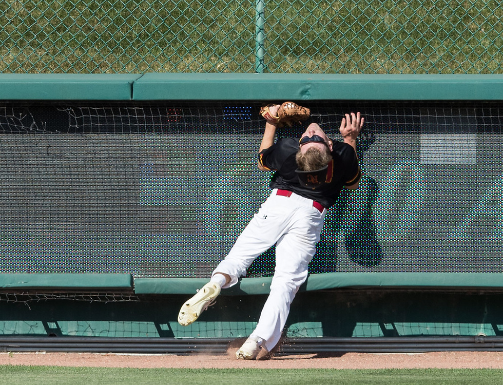 Roncalli left fielder Justin Niederle collides with the wall after catching a fly ball by Norris' Caden Agro in the fourth inning. Roncalli played Norris in a Class B playoff game at Haymarket Park on Wednesday, May 16, 2018, in Lincoln.<br /> <br /> MATT DIXON/THE WORLD-HERALD