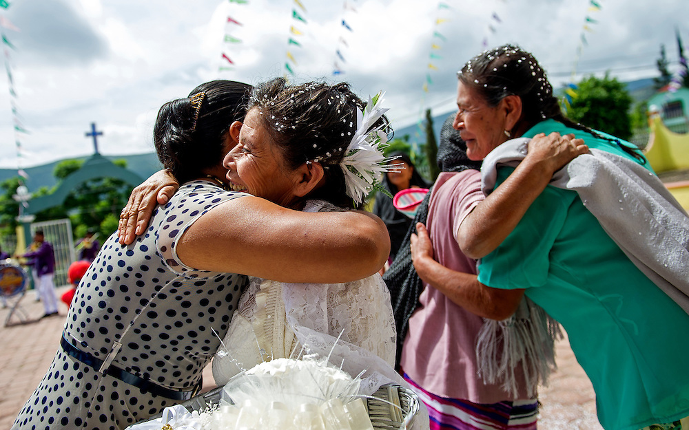 """In this July 23, 2016 photo, a woman hugs 65-year-old newlywed Francisca Santiago, second left, after marrying her life-long partner Pablo Ibarra, 75, in a religious ceremony at the Catholic church in Santa Ana, in the Mexican state of Oaxaca. """"It was beautiful, everything I hoped for,"""" Santiago said. """"Now we are together with the blessing of God."""" NICK WAGNER / ASSOCIATED PRESS"""