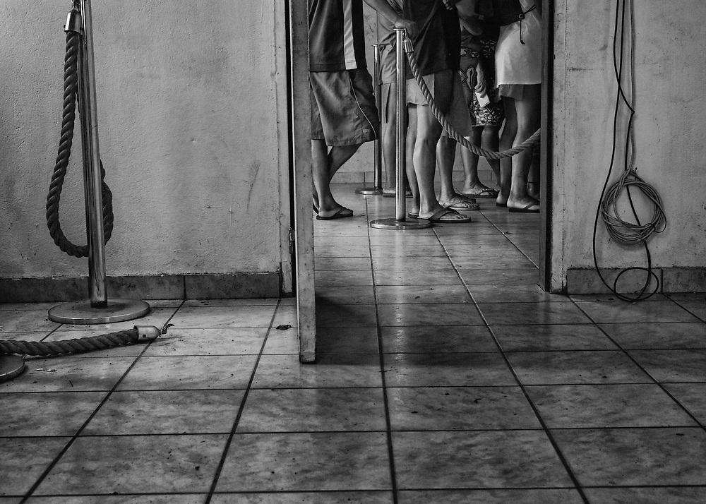 Camopi, Guyane, 2015.<br /> <br /> Jour du versement des allocations à la Poste de Camopi. Les perspectives professionnelles de la commune sont rares. Seule une cinquantaine d'emplois sont répartis entre la gendarmerie et la légion qui utilisent une dizaine de piroguiers, la poste qui occupe un salarié, le nouveau Parc National de Guyane, l'école, la municipalité et le département. A Camopi, pratiquement la totalité de la population active perçoit le RSA et les allocations familiales. <br /> <br /> La continuité du service bancaire se résume à la seule présence d'un bureau de Poste dont les caisses sont souvent vides en dehors des périodes de versement des prestations sociales. L'argent arrive alors par hélicoptère et peu avant le 7 de chaque mois, au moment des allocations, des familles entières se déplacent sur le fleuve depuis les villages de Trois-Sauts ou les écarts de la rivière Camopi pour venir toucher leurs subsides de l'État.<br /> <br /> Considérée comme la commune la plus enclavée de Guyane, à Camopi les activités économiques sont quasi inexistantes. Il n'y a pas de commerce en dehors du restaurant réservé exclusivement à l'hébergement et aux repas des escadrons de Gendarmes mobiles qui se relaient sur place. L'argent est donc immédiatement dépensé à Vila Brasil, un village brésilien à l'origine clandestin, devenu district d'Oiapoque en 2011 et qui fait face au bourg. Construit dans un premier temps pour alimenter les sites d'orpaillages illégaux, ce comptoir vit maintenant de l'argent dépensé par les Amérindiens de la commune. Les habitants du bourg viennent s'y approvisionner, acheter du poisson et s'y enivrer en voisins, ceux des villages distants, après avoir fait le plein de produits de première nécessité y résident quelques jours, le temps de dépenser leurs salaires, avant de repartir titubants vers leurs pirogues.