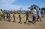 'Blanket feeding' for malnourished mothers and children. An Aid Worker  leads a group of malnourished children to line up up for food. Ajiep, Bahr el Ghazal, Sudan. The famine in Sudan in 1998 was a humanitarian disaster caused mainly by human rights abuses, as well as drought and the failure of the international community to react to the famine risk with adequate speed. The worst affected area was Bahr El Ghazal in southwestern Sudan. In this region over 70,000 people died during the famine.