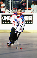 Model Released action photos of boys playing roller hockey on concrete floor.  Man inline skating with stick, puck, goalie in background.   Transparency slide scan. Tim Yuen.