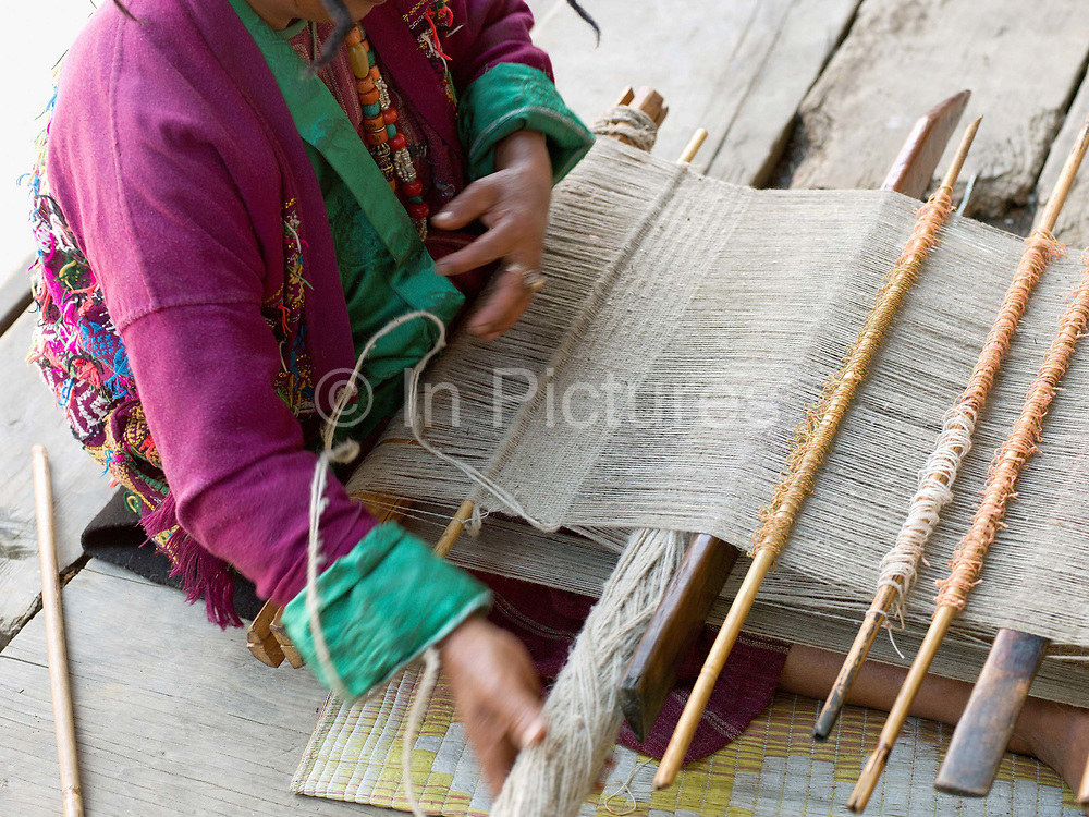 A Brokpa woman weaves a man's 'gho' (traditional tunic) from sheep wool on a backstrap loom in the remote and roadless village of Sakteng, Eastern Bhutan. The Brokpa, the semi-nomads of the villages of Merak and Sakteng are said to have migrated to Bhutan a few centuries ago from the Tshona region of Southern Tibet. Thriving on rearing yaks and sheep, the Brokpas have maintained many of their unique traditions and customs.
