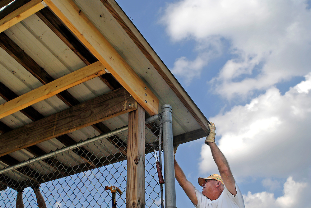 """Horseshoes and hand grenades,"""" Steve Humphreys jokes as he adjusts a roof panel on the dugout. He pulls the wood another inch to the left, then down, then up, trying to get it flush with another panel. Hammers hang from the chain link fence where bats normally hang. Ladders and drills, extension cords and screws litter the ground underneath the bench.<br /> <br /> Steve and two other Little League dads have taken off work the first day of fall to make a dent in the list of field improvements at the Daniel Boone Little League complex. """"We thought we'd spend some time together to do something good for the kids,"""" says Kevin Harrison.<br /> <br /> College students help out with labor over the summer. """"Moms and dads do the work the rest of the year,"""" Tim James explains.<br /> <br /> They've recycled the roof from the old Challenger Field dugout, stretching their $15,000 annual facilities budget a little further. They joke with each other as they secure the roofing in place. They talk about football. They brag about the league's accomplishments.<br /> <br /> In six hours, the job is done. The roof will protect the kids from the sun and foul balls. The league's 50th anniversary is next year, and they have plans for more improvements. The main concession stand needs work. The junior field dugouts are aging. With a day off here and there, the moms and dads are getting the job done."""