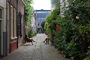 People enjoying the summer weather in an alleyway in Urecht, Netherlands
