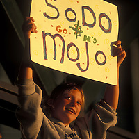 USA, Washington, Young girl holds sign cheering on Seattle Mariners at baseball game at Safeco Field on summer evening