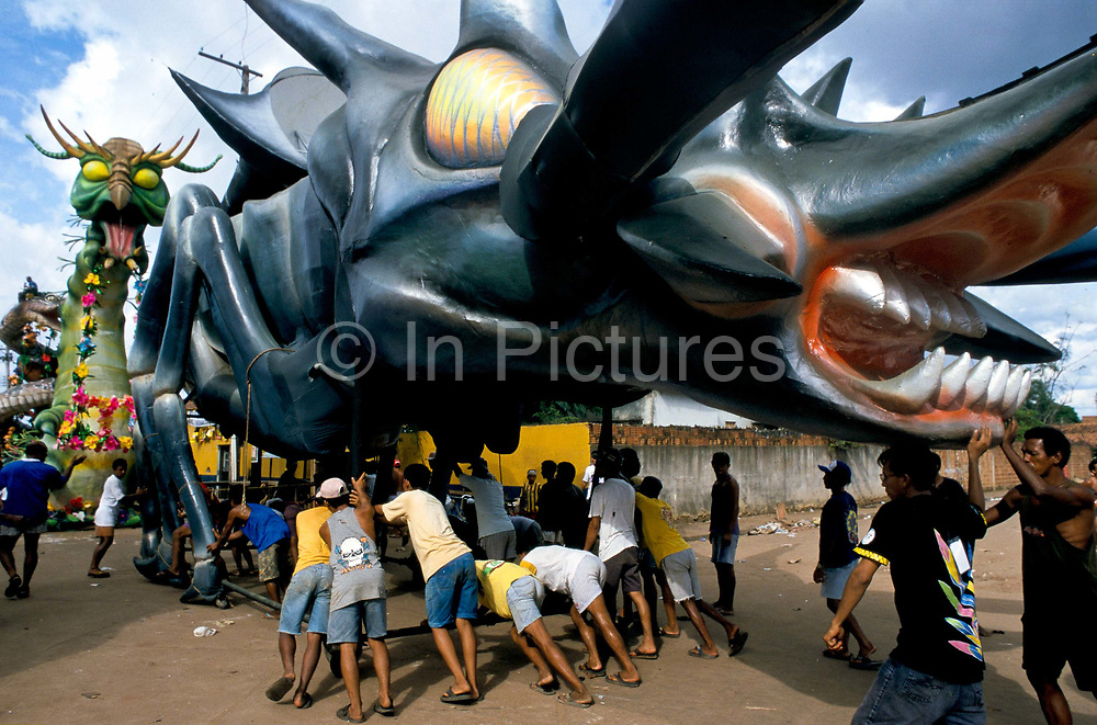 """A oversized Caterpiller  and dragon leaves a warehouse to enter the """"Bumbodromo"""", the stadium where the """"Boi Bumba"""" Carnival takes place, Parintins, Brazil. The carnival serves to celebrate and re-enact Indian traditions and perpetuate myths and legends. It has evolved over time and involves the battle between to opposing bulls, known as Garantido and Caprichoso."""