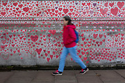 A woman wearing a red jacket walks past the National Covid memorial wall, a sea of red love hearts remembering all those who have died due to the COVID-19 pandemic on the 25th of May 2021 on the south bank in London, United Kingdom. Over 150,000 people have lost their lives in the United Kingdom due to the pandemic, the wall is a space for them to be remembered. (photo by Andrew Aitchison / In pictures via Getty Images)