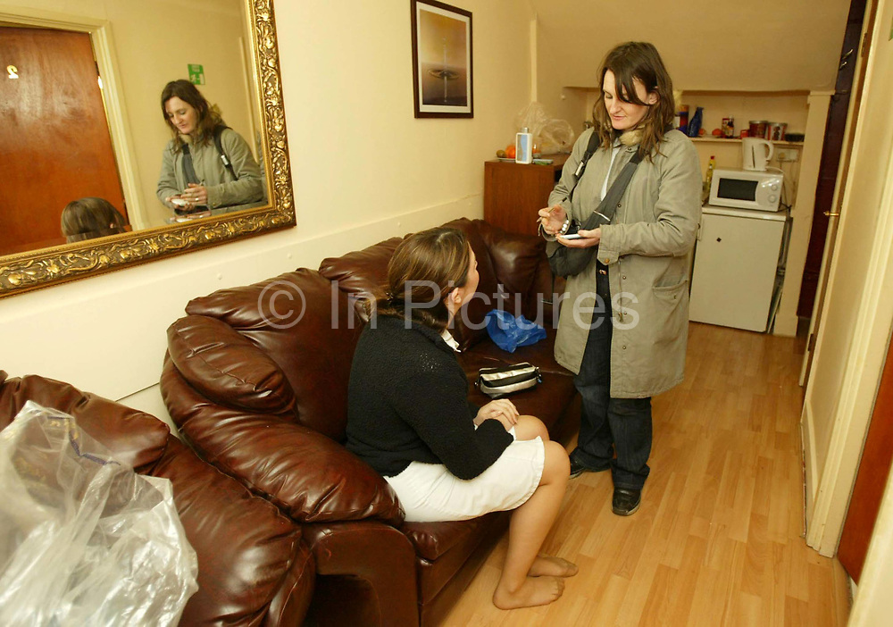 """A Police officer from the clubs and vice unit (R) interviews a woman during a raid on the 'Ishka' sauna. 'Ishka' Sauna, Hampden road, Honesey, North London. Scene where a milti million pound vice ring was centred by Josephine Daly. Josephine Daly was thought to have been an eccentric woman who named her house after a pet dog she had buried in the garden. Rarely seen outdoors or driving her white Rolls-Royce, the bespectacled 64-year-old hardly aroused suspicion in Hornsey. But when detectives began investigating one of the capital's biggest vice rings, they soon discovered """"Josie"""" was not what she seemed. Over more than a decade, the quietly spoken Irish woman had built up a prostitution empire based at three saunas which was earning her an alleged £3-4m a year.<br /> Only one of the premises actually had a sauna. Undercover officers were offered a sex menu after paying a £10 entry fee and ushered into a massage room where they made their excuses and left. A surveillance operation showed 1,500 men were going to the brothels at Aqua Sauna, Lanacombe Sauna, and the Ishka Bath every week."""