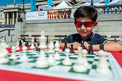 © Licensed to London News Pictures. 18/07/2021. LONDON, UK. David, aged 5, plays takes part in speed chess against a grandmaster at Chess Fest in Trafalgar Square.  The event celebrates the game of chess and visitors can learn the game, play chess or challenge a Grandmaster.  Also, to celebrate the 150th anniversary of Lewis Carroll's Alice Through the Looking Glass book which featured the game of the chess, 32 actors dressed as Alice Through the Looking Glass characters stand on a giant chessboard replaying a game based on the book.  Photo credit: Stephen Chung/LNP