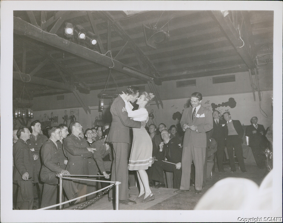 1943 Betty Grable kisses a serviceman on the stage at the Hollywood Canteen