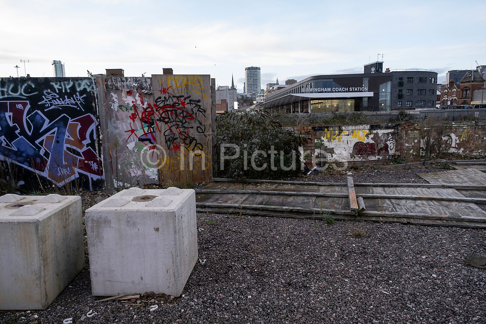 View looking towards the iconic Rotunda building across overgrown and disused waste ground next to Digbeth Coach Station, which seems to have stalled awaiting redevelopment in the last year in the industrial area of Deritend, which lies less than half a mile from the city centre on 14th December 2020 in Birmingham, United Kingdom. Birmingham is undergoing a massive transformation called the Big City Plan which involves the controversial regeneration of the city centre as well as a secondary zone reaching out further. The Big City Plan is the most ambitious, far-reaching development project being undertaken in the UK. The aim for Birmingham City Council is to create a world-class city centre by planning for the next 20 years of transformation.