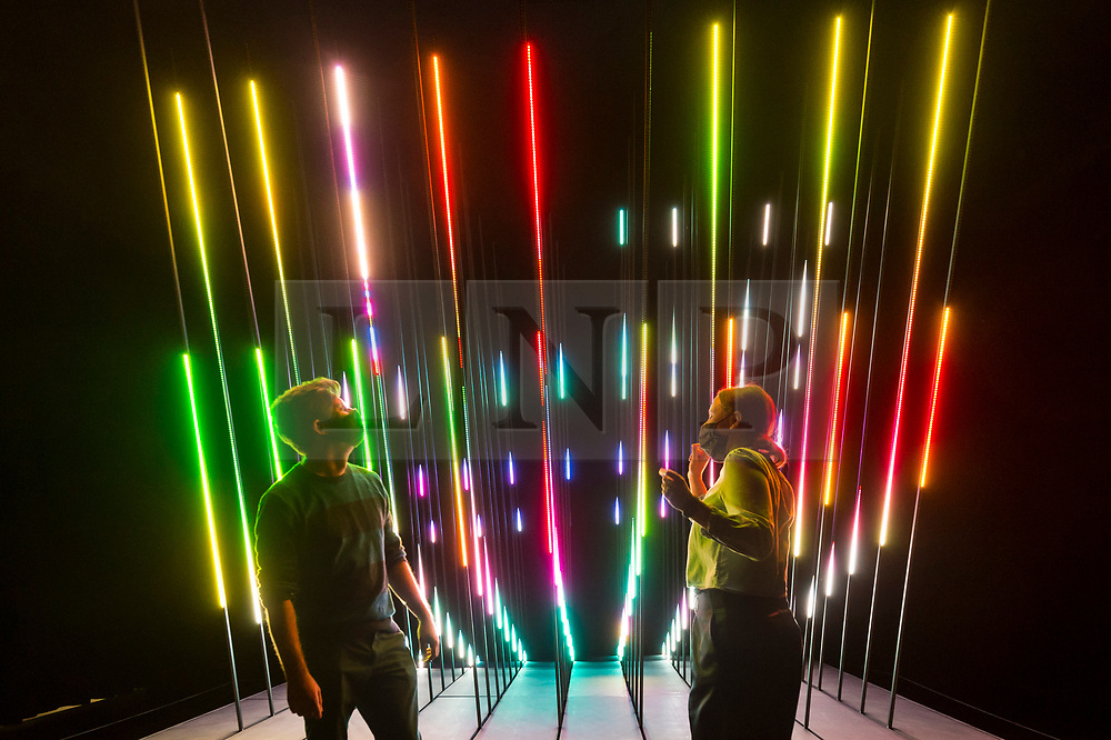 """© Licensed to London News Pictures. 28/07/2020. CITY, UK.  Staff members pose in front """"CORE"""", 2019, by 1024 Architecture, an audio visual LED installation.  Preview of """"Electronic: From Kraftwerk to The Chemical Brothers"""" at the Design Museum in Kensington which is reopening after coronavirus lockdown.  The new exhibition explores the hypnotic world of electronic music, from its origins to its futuristic dreams.  The show runs 31 July 2020 – 14 February 2021 with visitors required to adhere to strict social distancing guidelines.  Photo credit: Stephen Chung/LNP"""