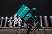 Deliveroo cycle courier with his large back box interacts with a stencilled cyclist while out delivering in London, England, United Kingdom. (photo by Mike Kemp/In Pictures via Getty Images)