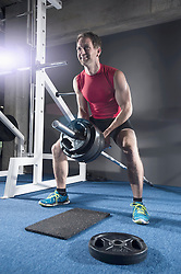 Mid adult man doing bent over row exercising with long barbell in the gym, Bavaria, Germany